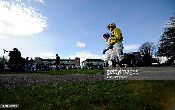 Jockeys Jake Hodson and Andrew Thornton make their way to the parade ring at Fontwell racecourse on March 15 2014 in Fontwell England