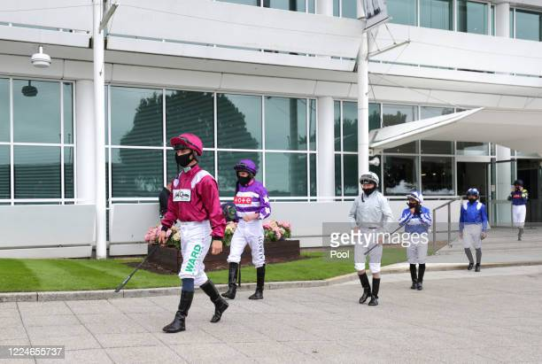 Jockeys make their way out ahead of the Investec Surrey Stakes at Epsom Racecourse on July 04, 2020 in Epsom, England. The famous race meeting will...