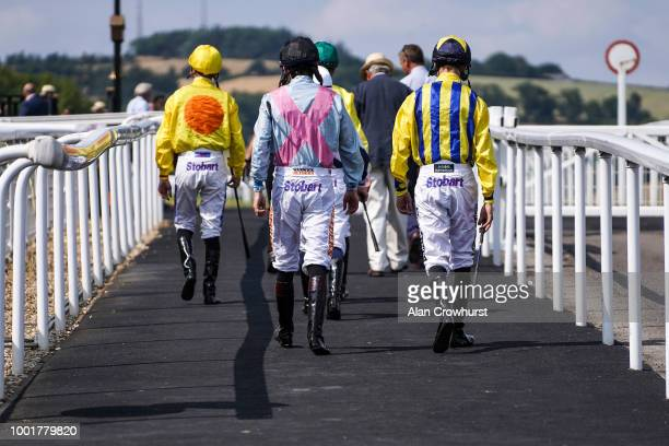 Jockeys make their way to the parade ring at Chepstow Racecourse on July 19 2018 in Chepstow Wales