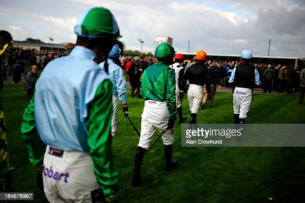 Jockeys make their way to the parade ring at Huntingdon racecourse on October 15 2013 in Huntingdon England