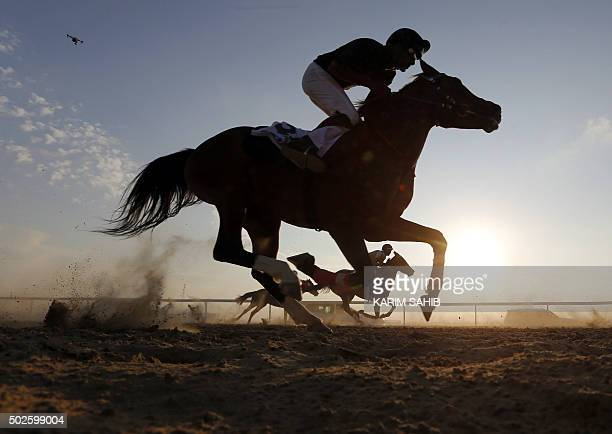 Jockeys race purebred Arabian horses on the sidelines of the Mazayin Dhafra Camel Festival in the desert near the city of Madinat Zayed 150 kms west...