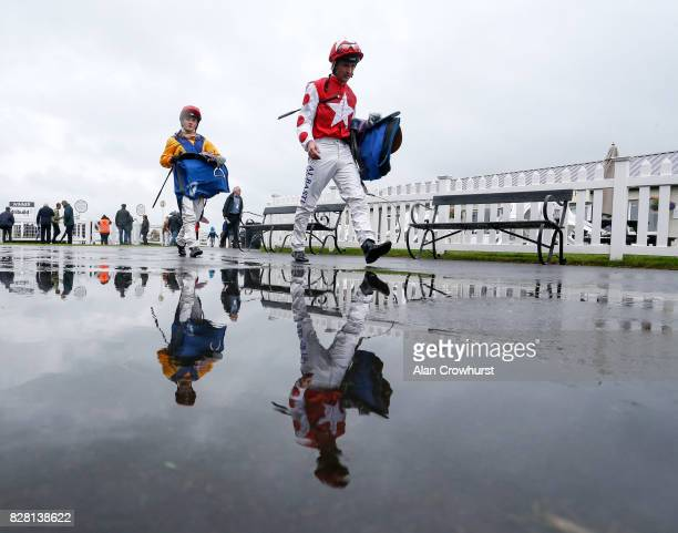 Jockeys return to the weighing room on a wet day at Bath racecourse on August 9 2017 in Bath England