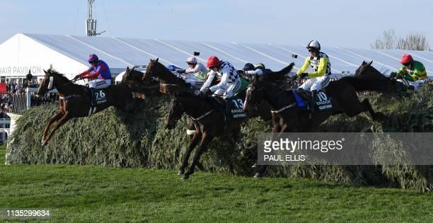 Jockeys ride their horse over a fence as they compete in the Grand National Handicap Chase horse race on the final day of the Grand National Festival...