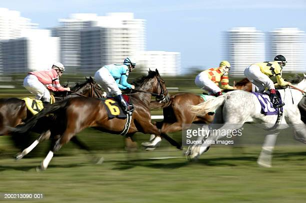 jockeys riding horses in race (blurred motion) - racehorse stock pictures, royalty-free photos & images