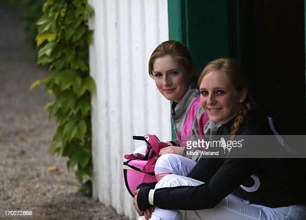 Jockeys Shannon Spratter and Alina Pinzner wait outside the jockeys room during the Lotto Festival 2013 at Galopp Munich on June 9 2013 in Munich...