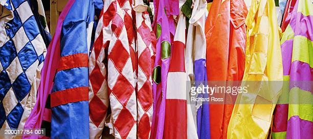 jockey's silks hanging in jockey room, close-up - jockey silks stock pictures, royalty-free photos & images