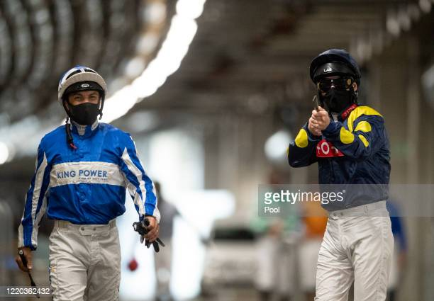 Jockey's Silvestre De Sousa and Martin Dwyer walk through the service tunnel from the auxiliary weighing room towards the paddock at Ascot Racecourse...