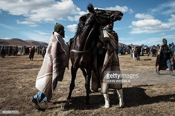Jockeys try to control a horse as they wait for the races to start on July 16 2016 in Semonkong Horseracing in the mountain kingdom of Lesotho is not...