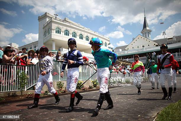 Jockeys walk in the paddock area prior to the 141st running of the Kentucky Derby at Churchill Downs on May 2 2015 in Louisville Kentucky