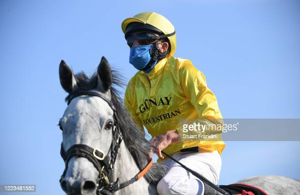 Jockeys wearing mouth and nose protection are seen on May 07, 2020 in Hanover, Germany. The performance test is the first horse race since the...