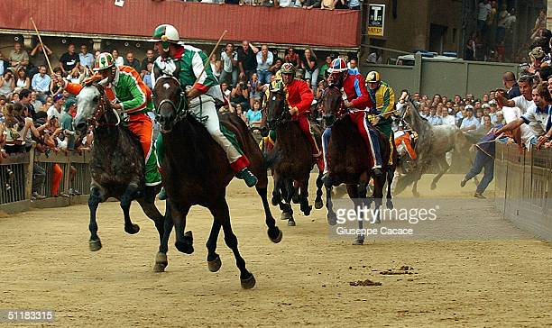 Jockeys wearing the colours of their Contrade ride horses in Piazza del Campo during the Palio horse race on August 16 2004 in Siena Italy The city's...