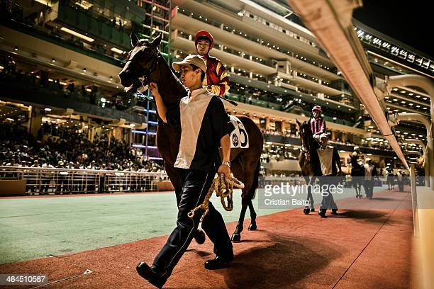 Jockeys with their horses at the Happy Valley racetrack in Hong Kong