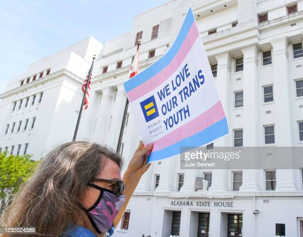 """Jodi Womack holds a sign that reads """"We Love Our Trans Youth"""" during a rally at the Alabama State House to draw attention to anti-transgender..."""