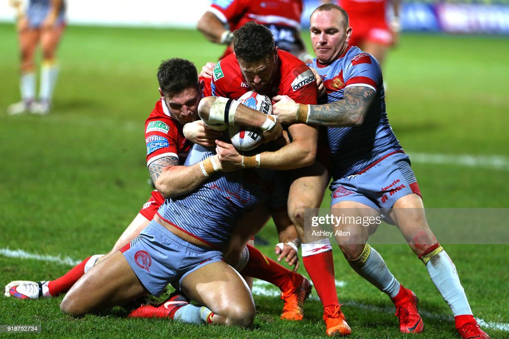Jodie Broughton (C) of the Catalans Dragons is tackled by Hull KR's Thomas Minns and Kieren Moss as Catalans Dragons Luke Walsh (R) attempts to win the ball during the BetFred Super League match between Hull KR and Catalans Dragons at KCOM Craven Park on February 15, 2018 in Hull, England.