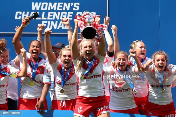 Jodie Cunningham of St Helens lifts the Betfred Women's Challenge Cup trophy as her team mates celebrate after during the Betfred Women's Super...