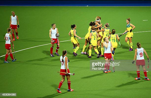 Jodie Kenny of Australia celebrates with her teammates after scoring a goal with 16 seconds left as England look dejected during the Women's Gold...