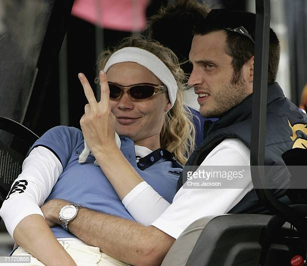Jodie Kidd sits on her husband Aiden Butler's lap in a golf cart on the first day of the Northern Rock All Star Cup at the Celtic Manor Resort on...