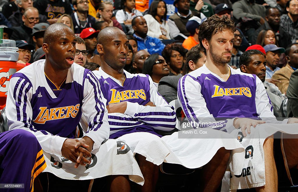 Jodie Meeks #20, Kobe Bryant #24, and Pau Gasol #16 of the Los Angeles Lakers watch in the first half during the game against the Atlanta Hawks at Philips Arena on December 16, 2013 in Atlanta, Georgia.
