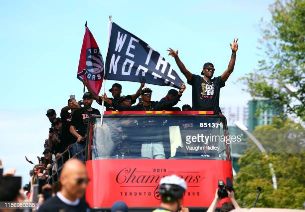 Jodie Meeks, Malcolm Miller and Serge Ibaka of the Toronto Raptors wave from their bus during the Toronto Raptors Victory Parade on June 17, 2019 in...