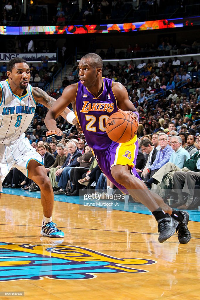 Jodie Meeks #20 of the Los Angeles Lakers drives against Roger Mason Jr. #8 of the New Orleans Hornets on March 6, 2013 at the New Orleans Arena in New Orleans, Louisiana.
