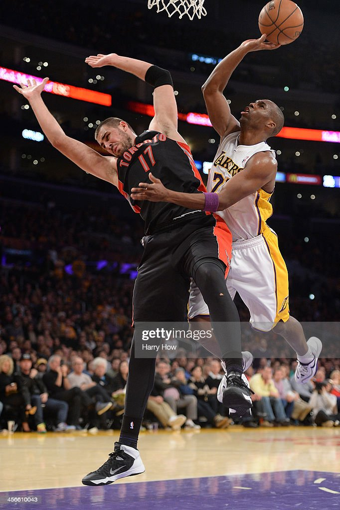 Jodie Meeks #20 of the Los Angeles Lakers drives on Jonas Valanciunas #17 of the Toronto Raptors at Staples Center on December 8, 2013 in Los Angeles, California.