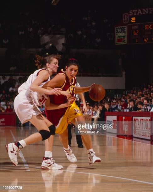 Jody Anton, Forward for the University of Southern California Trojans dribbles the ball past the challenge of Kate Starbird, Forward for the...
