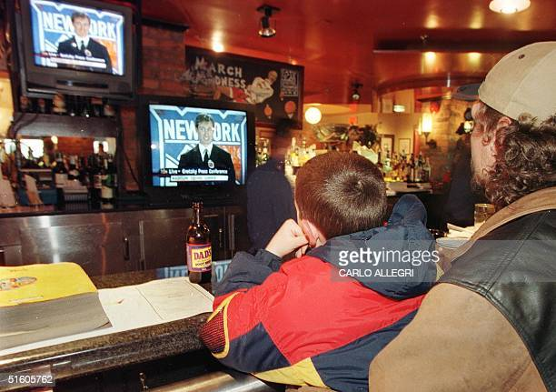 Jody Easton and his nineyearold son Cody watch televisions inside Wayne Gretzky's restaurant called Wayne Gretzky's 16 April 1999 in Toronto as...
