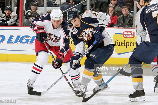 Jody Shelley of the Columbus Blue Jackets and Jordin Tootoo of the Nashville Predators get tangled up while battling for the puck on December 23 2007...