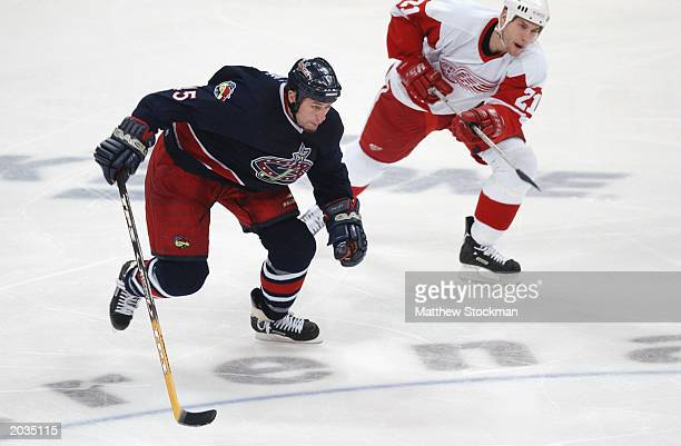 Jody Shelley of the Columbus Blue Jackets chases down the puck along with Boyd Devereaux of the Detroit Red Wings on December 23, 2002 at Nationwide...
