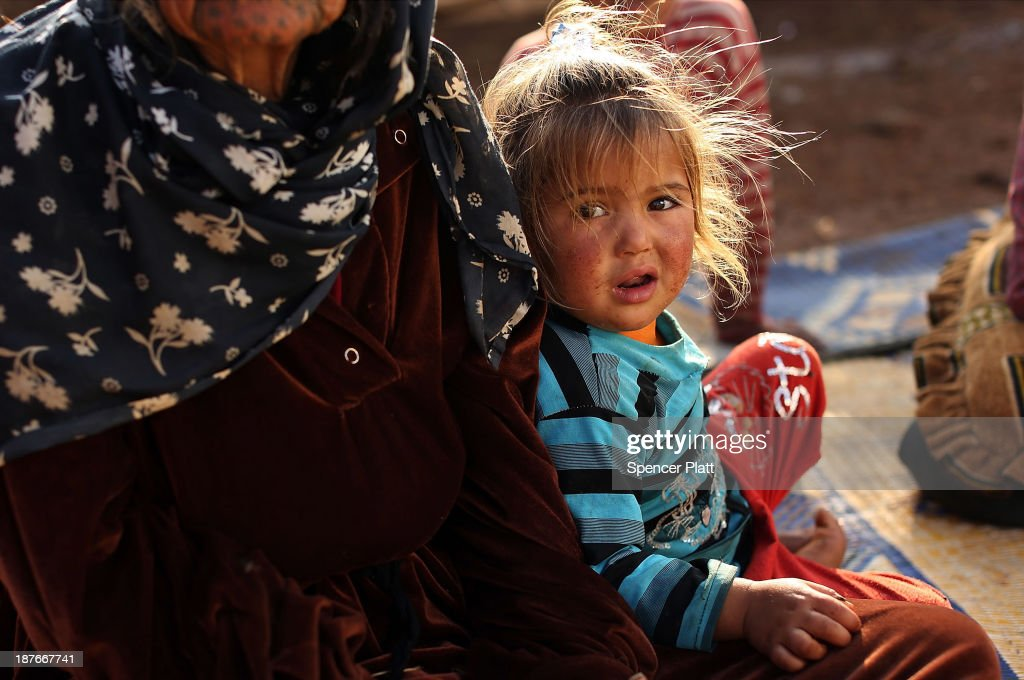 Jody (10 months) sits with her family who recently arrived from the besieged Syrian city of Aleppo in a makeshift camp in the Bekaa Valley, close to the border with Syria on November 11, 2013 in Majdal Anjar, Lebanon. As the war in neighboring Syria drags on for a third year, Lebanon, a country of only 4 million people, is now home to the largest number of Syrian refugees who have fled the conflict. The situation is beginning to put huge social and political strains on Lebanon as there is currently no end in sight to the war in Syria.
