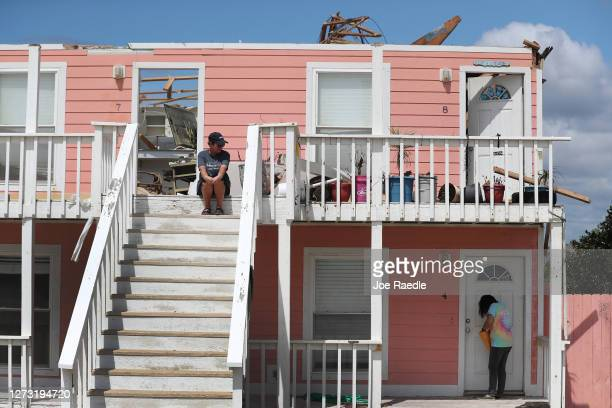 Jody Wright sits on the steps leading to her apartment as Christine Cortaza the property manager checks on the building after the roof was damaged...