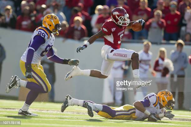 Joe Adams of the Arkansas Razorbacks jumps over a defender after making a catch against the LSU Tigers at War Memorial Stadium on November 27, 2010...
