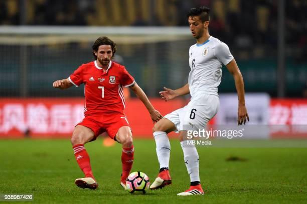 Joe Allen left of Wales national football team kicks the ball to make a pass against Rodrigo Bentancur of Uruguay national football team in their...