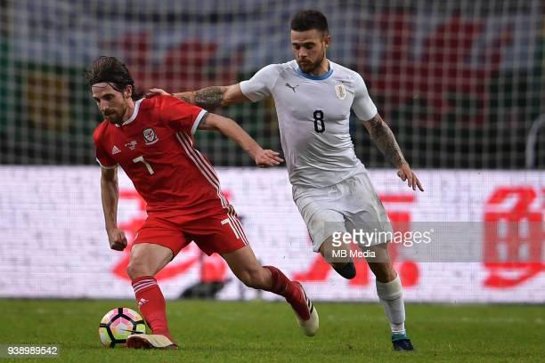 Joe Allen left of Wales national football team kicks the ball to make a pass against Nahitan Nandez of Uruguay national football team in their final...