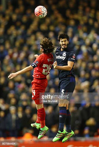 Joe Allen of Liverpool and James Tomkins of West Ham United clash heads as they jump for a header during the Emirates FA Cup Fourth Round match...