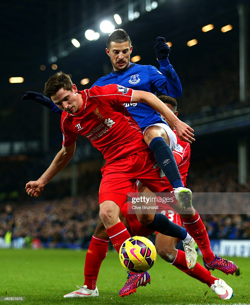 Joe Allen of Liverpool battles for the ball with Kevin Mirallas of Everton during the Barclays Premier League match between Everton and Liverpool at Goodison Park on February 7, 2015 in Liverpool, England.