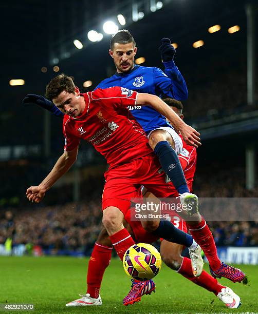 Joe Allen of Liverpool battles for the ball with Kevin Mirallas of Everton during the Barclays Premier League match between Everton and Liverpool at...