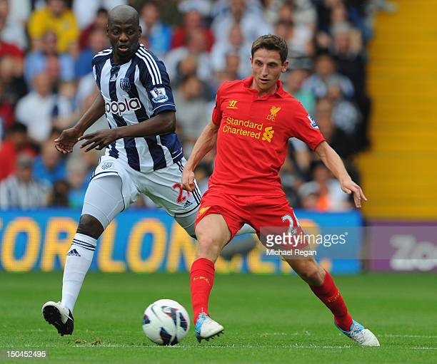 Joe Allen of Liverpool battles Youssouf Mulumbu of West Brom during the Barclays Premier League match between West Bromwich Albion and Liverpool at...
