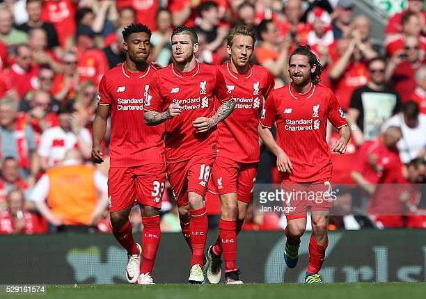 Joe Allen of Liverpool celebrates with his team mates after scoring his side's first goal during the Barclays Premier League match between Liverpool...