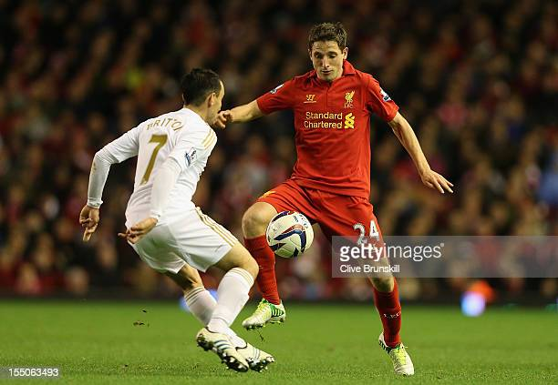 Joe Allen of Liverpool competes with Leon Britton of Swansea City during the Capital One Cup Fourth Round match between Liverpool and Swansea City at...