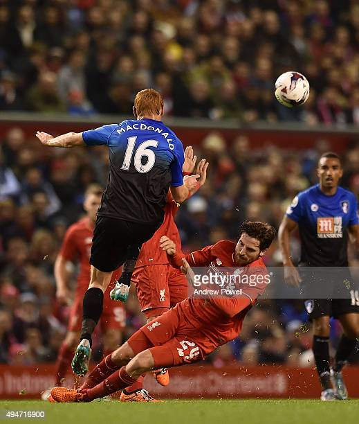 Joe Allen of Liverpool competes with Shaun MacDonald of AFC Bournemouth during the Capital One Cup Fourth Round match between Liverpool and AFC...