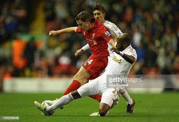 Joe Allen of Liverpool is challenged by Dwight Tiendalli of Swansea City during the Capital One Cup Fourth Round match between Liverpool and Swansea...