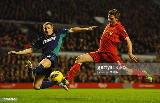 Joe Allen of Liverpool shoots under pressure from Matthew Kilgallon of Sunderland during the Barclays Premier League match between Liverpool and...