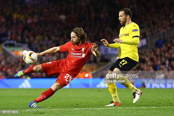 Joe Allen of Liverpool shoots with Gonzalo Castro of Borussia Dortmund during the UEFA Europa League quarter final second leg match between Liverpool...
