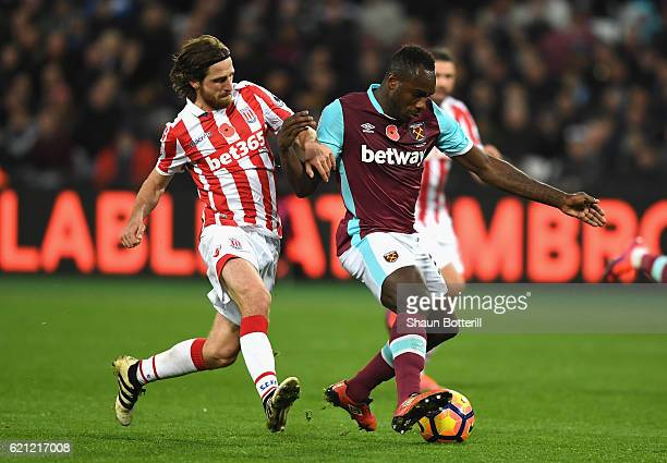 Joe Allen of Stoke City and Michail Antonio of West Ham United battle for possession during the Premier League match between West Ham United and...