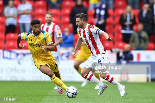 Joe Allen of Stoke City is challenged by Josh Laurent of Reading FC during the Sky Bet Championship match between Stoke City and Reading at Bet365...