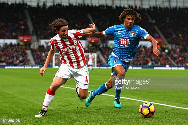 Joe Allen of Stoke City is put under pressure from Nathan Ake of AFC Bournemouth during the Premier League match between Stoke City and AFC...