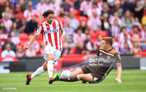 Joe Allen of Stoke City is tackled by Lewis MacLeod of Brantford during the Sky Bet Championship match between Stoke City and Brentford at Bet365...