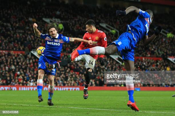Joe Allen of Stoke City Jesse Lingard of Manchester United and Kurt Zouma of Stoke City miss a header during the Premier League match between...