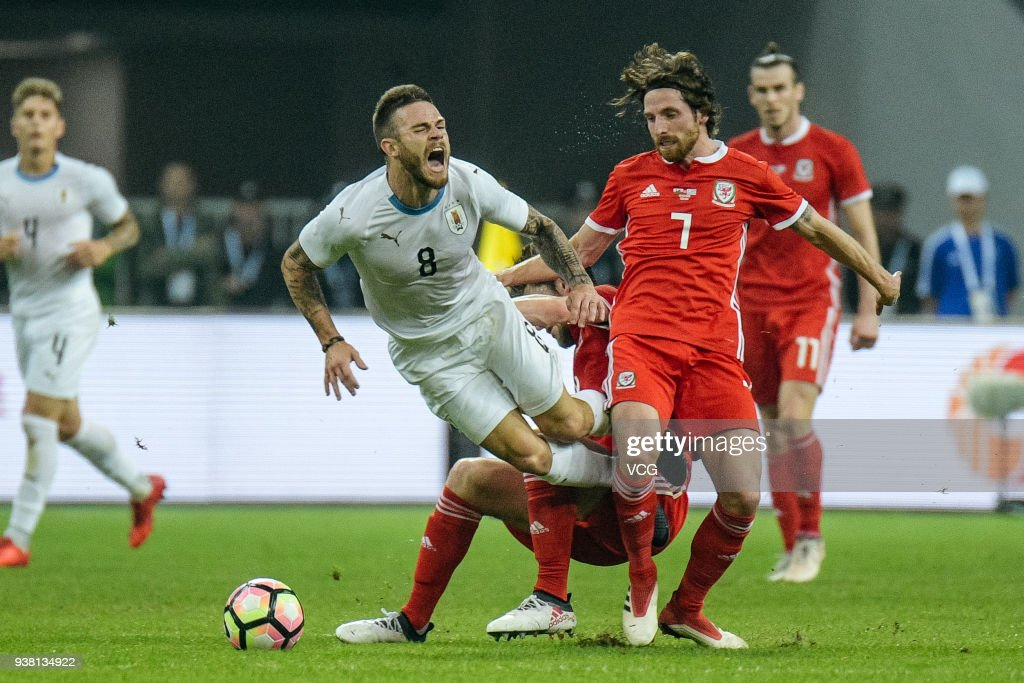 Joe Allen #7 of Wales and Nahitan Nandez #8 of Uruguay compete for the ball during the 2018 China Cup International Football Championship match between Wales and Uruguay at Guangxi Sports Center on March 26, 2018 in Nanning, China.